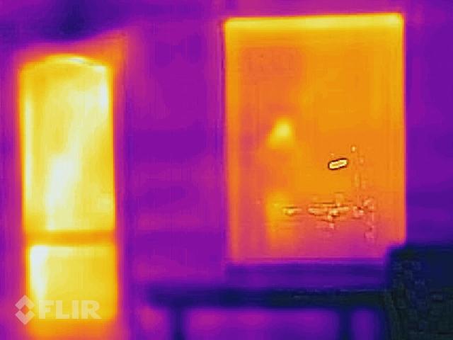 Tuvāks skats uz loga un durvju ailu, telpas sakurinātas līdz 24C, ārā - mīnus 12C. Redzams, ka siltais gaiss ceļas augšup - tuvāk pie griestiem stiklpakete siltāka, kā palodzes līmenī. Ailu ārējā apdare vēl nav pabeigta.