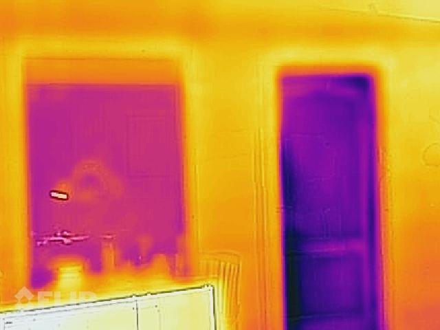 Termogrāfijas attēli - darbnīcas skats no iekšpuses - labajā pusē redzamas durvis, kas salīdzinoši ir krietni aukstumu caurlaidīgākas par kreisajā pusē redzamo loga ailu kurā iebūvēta 3 kārtu stikla pakete bezrāmja tehnoloģijā.