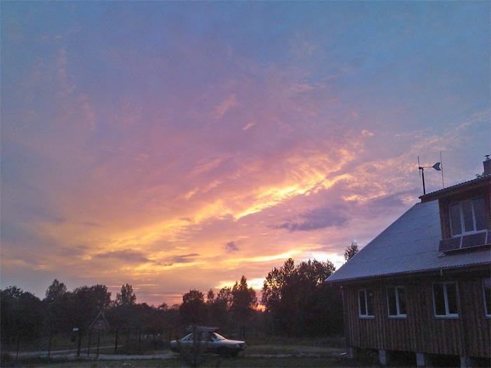 Saimniecības ēkas projekta realizācijas gaita un foto ar vēja ģeneratoru saulrietā